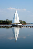 Reflected sailboat. A yacht is reflected in the calm water on a lazy summer day Stock Images