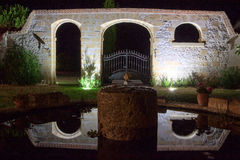 Reflected stone arched gateway. Night photo of stone arch with wrought iron gate in French garden, reflected in pond Stock Images