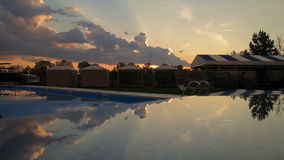 Reflected sunset and clouds over the swimming pool stock video footage