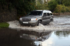 Reflected SUV. SUV driving through a flood royalty free stock photo