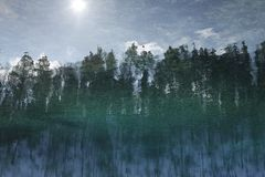 Reflected in the water with ripples landscape, forest, sky