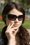 Reflecting Girl. A portrait a young adult woman in dark sunglasses Royalty Free Stock Photography