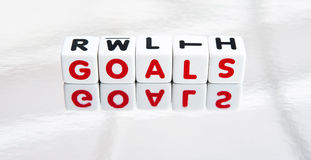 Reflecting on goals in life. Text ' goals ' in red uppercase letters inscribed on small white cubes placed on a reflecting surface, bright background Stock Images