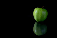 Reflecting green apple on a black background Stock Photos