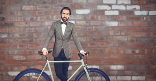 Reflecting hipster man with a bike in front of red stone wall Royalty Free Stock Photography