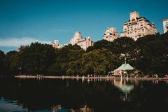 A reflecting lake in a park with tall buildings and beautiful sky. A reflecting lake in a park with tall buildings, trees and a beautiful sky stock photos