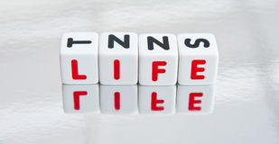 Reflecting on life. Text ' life ' in uppercase red letters inscribed on small white cubes and reflected in a mirror, white background Royalty Free Stock Photography