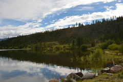Reflecting Mountain Lake Water. Mountainside with trees reflecting in a lake Royalty Free Stock Photos