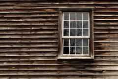 Reflecting On The Past. Closeup of an old Grist-Mill showing reflections in the window Stock Image