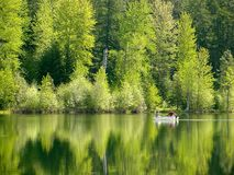Reflecting Pond. Two people fishing on a spring day on a calm green lake.  Lavender Lake near Cle Elum, WA Royalty Free Stock Images