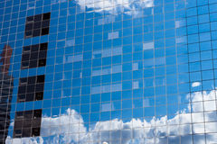 Reflecting sky in glass of office building Stock Photos