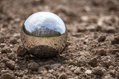Reflecting sphere on brown earth Royalty Free Stock Photography