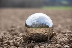 Reflecting sphere on brown earth Stock Photos