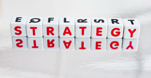 Reflecting on strategy. Text ' strategy ' in uppercase red letters inscribed on small white cubes shown with reflection in a mirror surface, white background Royalty Free Stock Photos