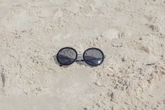 Reflecting sunglasses on the beach, glasses in the sand stock photo