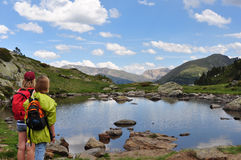 Reflecting on top of the world. Two girls looking at a pond high in the Pyrenees Mountains of Andorra. We hiked in this beautiful little country during our trip Stock Photography