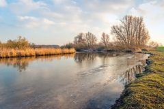 Reflecting wide creek in a Dutch nature reserve. It is still winter and some ice is at the edge of the water surface Royalty Free Stock Photography