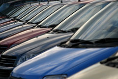 Reflecting windscreens from a row of cars. Reflecting windscreens from a row of different coloured cars Royalty Free Stock Images