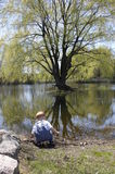 Reflection. A boy playing by a pond with a tree reflecting on the water Stock Photo