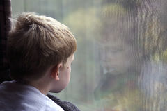 Reflection. A little boy looking out of the window.  The shot also shows his reflection Royalty Free Stock Photo