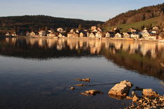 Reflection. Of a Town on a Serene Lake. Dusk Setting. Rocks provide perspective Stock Photo