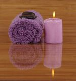 Reflection. Purple towel, pebbles, and candle on bamboo Stock Images
