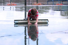 Reflection. Little boy looks at his reflection on the wet surface of a tennis court during rain Royalty Free Stock Image