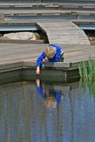 Reflection. Young boy standing next to a pond Stock Photography