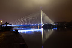 Reflection of Ada bridge and ship on Sava river. Belgrade at night, new bridge and ships on Sava river in the cloudy night, Most na Adi from Novi Beograd side of Stock Image