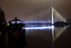 Reflection of Ada bridge and ship on Sava river. Belgrade at night, new bridge and ships on Sava river in the cloudy night Stock Photo