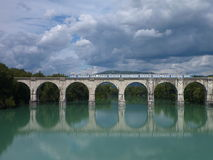 Reflection of an arched bridge with train Stock Photo