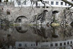 Reflection of arches, windows and cliff on a river. Stock Photos