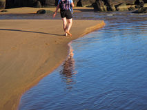 Reflection of a backpacker and footprints on sand Royalty Free Stock Photos