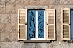 Reflection of bare tree in home window in spring. Travel to Italy - reflection of bare tree in home window on Upper town in Bergamo city, Lombardy in spring royalty free stock photography