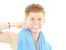 Reflection in a bathroom mirror of  young man brushing his teet Royalty Free Stock Images