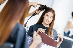Reflection of beautician doing haircut for woman Stock Photo