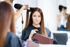 Reflection of beautician doing hairdo for woman Royalty Free Stock Photo