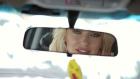 Reflection of a beautiful girl in a mirror of car. stock footage