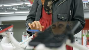 Reflection of a beautiful girl in the phone screen, a woman holding a smartphone in an electronics store. Reflection of a pretty girl in the phone screen, an stock video