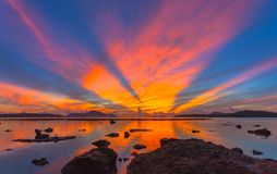 Reflection of beautiful sunrise in Rawai sea. Scenery reflection of beautiful sunrise in Rawai sea. amazing morning light shines through the colorful sky royalty free stock image