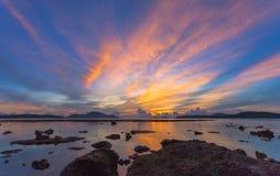 Reflection of beautiful sunrise in Rawai sea. Scenery reflection of beautiful sunrise in Rawai sea. amazing morning light shines through the colorful sky stock image
