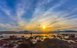 Reflection of beautiful sunrise in Rawai sea. Scenery reflection of beautiful sunrise in Rawai sea. amazing morning light shines through the colorful sky royalty free stock photography