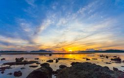 Reflection of beautiful sunrise in Rawai sea. Scenery reflection of beautiful sunrise in Rawai sea. amazing morning light shines through the colorful sky royalty free stock photo