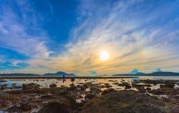 Reflection of beautiful sunrise in Rawai sea. Scenery reflection of beautiful sunrise in Rawai sea. amazing morning light shines through the colorful sky stock photo