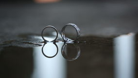Reflection of beautiful wedding rings in a puddle stock video footage