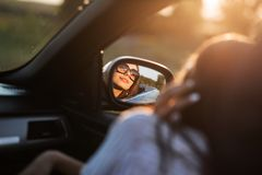 Reflection of a beautiful young dark-haired girl in sunglasses in a side mirror of a car. stock photography