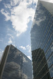 Reflection of blue sky. Clear blue sky with clouds reflected between two office buildings Stock Photography