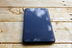 Reflection of blue sky with white clouds on the smartphone screen on a wooden background in blur stock image