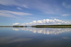 Reflection of blue sky with white clouds in water Stock Photo