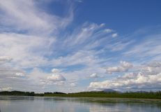 Reflection of blue sky with white clouds in water Stock Photos